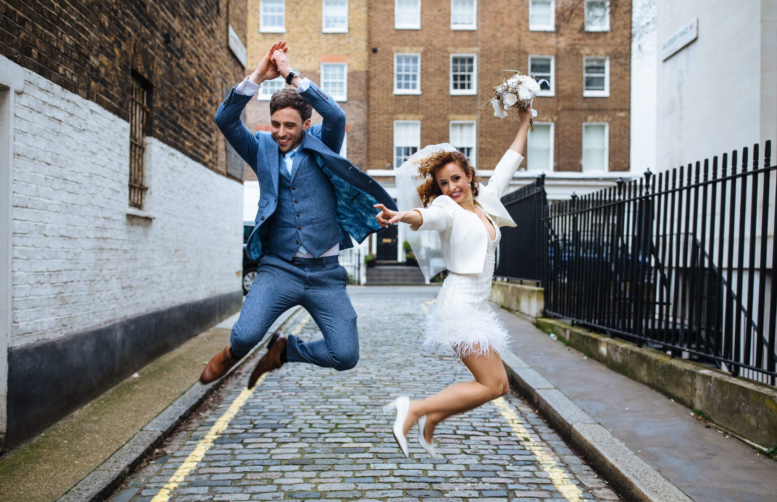bride and groom jumping for joy at Marylebone town hall wedding