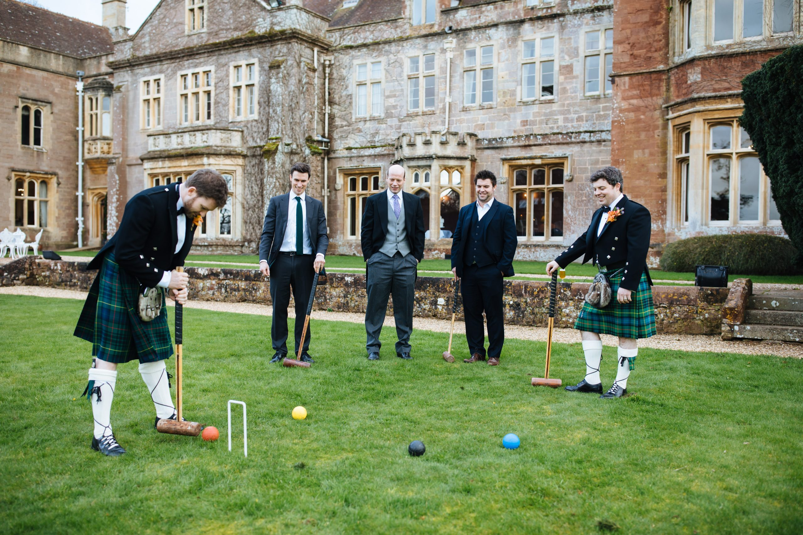 groomsmen playing croquet in kilts at St Audries park wedding
