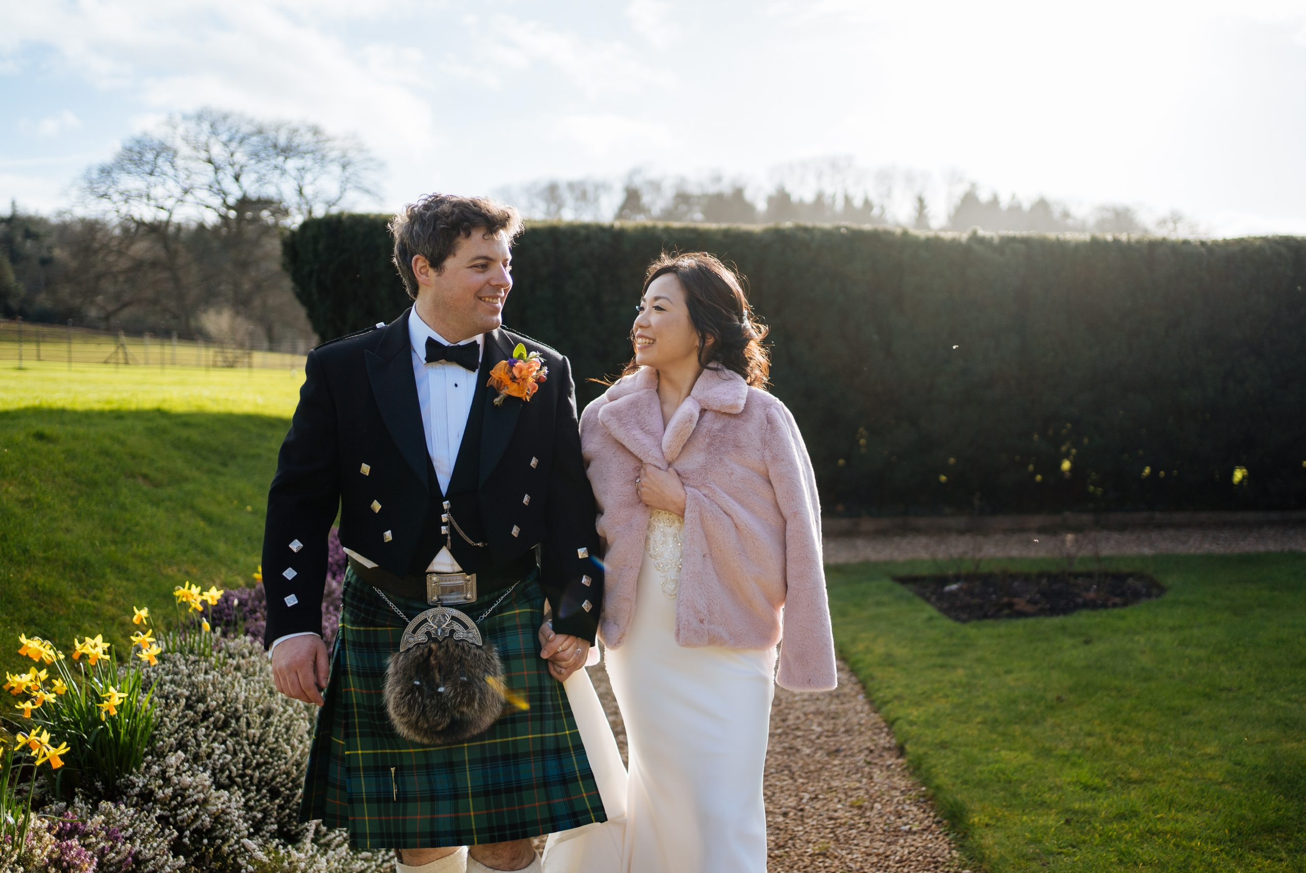groom and bride in pink coat walking at st audries park wedding